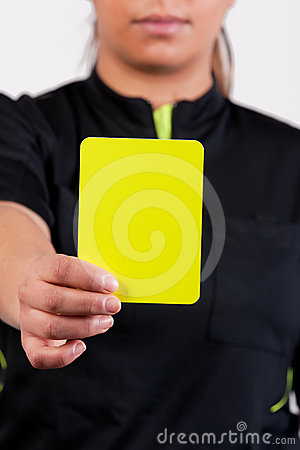 Árbitro do futebol que mostra o cartão amarelo
