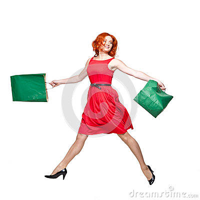 Readhead with green shopping bags jumping