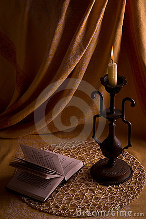 Reading of the book by the light of a candle.