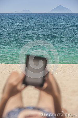Reading from e-reader relaxing on the beach