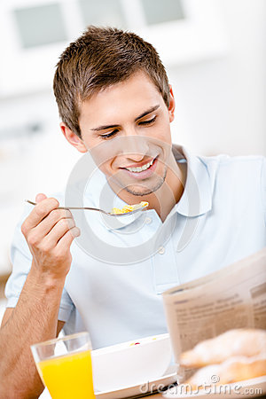 Reading male eats dieting breakfast in kitchen