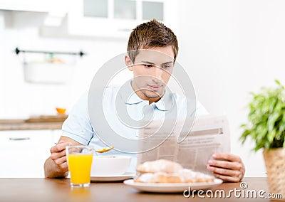 Reading man eats light breakfast in kitchen