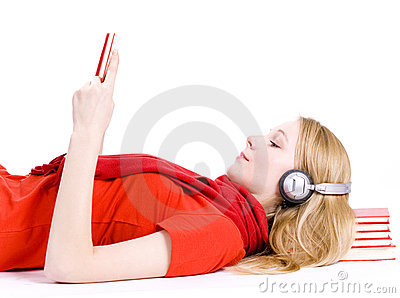 Reading woman in headphones lying on heap of books