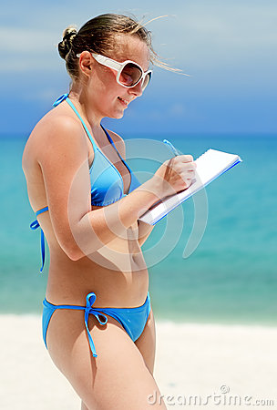 Young woman with notebook on a beach