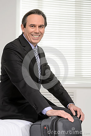 Ready to go. Cheerful mature businessman sitting on the sofa at