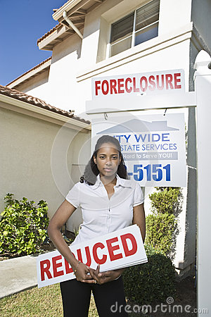 Real Estate Agent Holding Sign Board Outside House