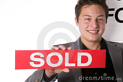 Real estate agent holding a Sold sign