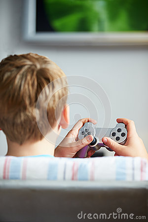 Rear View Of Boy Holding Controller Playing Video Game