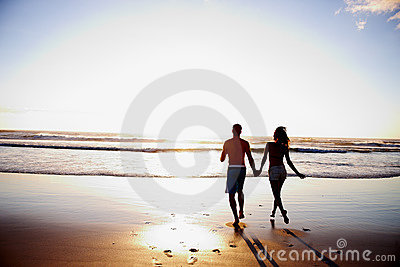 Rear view of a couple holding hands on the beach