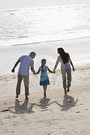 Rear view of family holding hands walking on beach