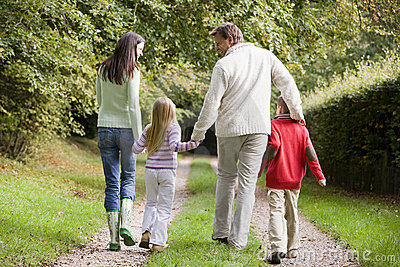 Rear view of family walking along track