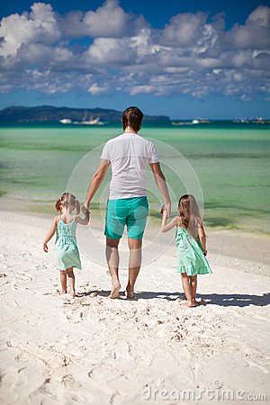 Rear view of father and his two cute daughters