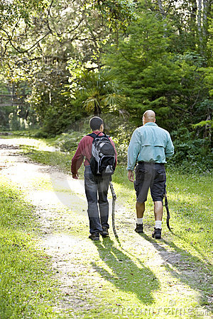 Rear view father and son hiking in woods on trail