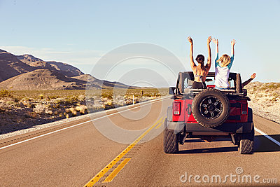 Rear View Of Friends On Road Trip Driving In Convertible Car Stock Photo