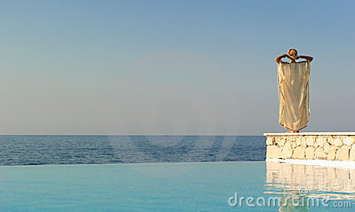 Rear view of greek style woman near infinity pool