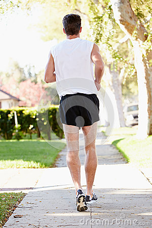 Rear View Of Male Runner Exercising On Suburban Street
