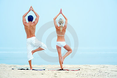 Rear view of a man and woman practicing yoga