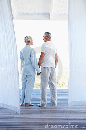 Rear view of a mature couple in love holding hands