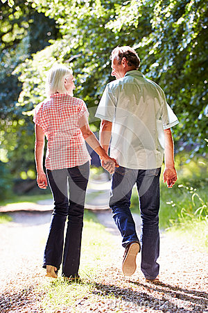 Rear View Of Middle Aged Couple Walking Along Country Lane