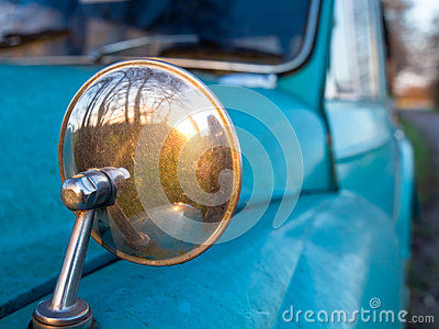 ... view mirror on a vintage car resembling looking back in time, concept