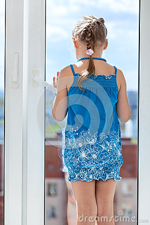Free Rear View Of Girl In Blue Dress Standing Behind Window Glass Royalty Free Stock Photography - 41449197