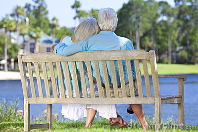Rear View Senior Couple Sitting On Park Bench