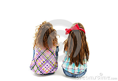 Rear view of two little girl sitting on floor and looking up