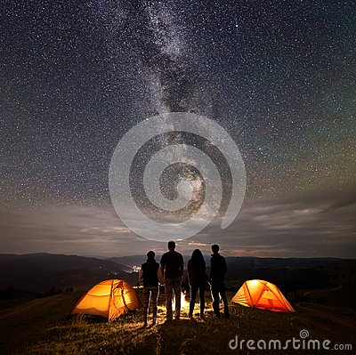 Free Rear View Two Young Couples At Night In Tent Camp Stand Enjoying Starry Sky, Milky Way, Mountains And Luminous Town Stock Photo - 116596650