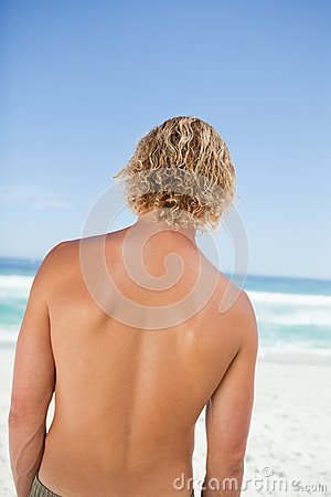 Rear view of a young blonde man looking at the ocean