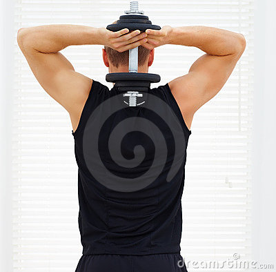Rear view of a young guy exercising his triceps