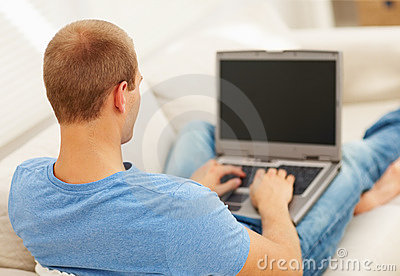 Rear view of young guy using laptop