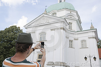 Rear view of young man photographing St. Casimir Church, Warsaw, Poland