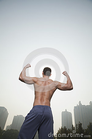Rear view of young, muscular man with no shirt on flexing his back muscles, outdoors in Beijing, China