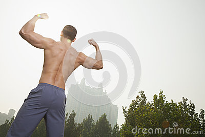 Rear view of young, muscular man with no shirt on flexing his back muscles, outdoors in Beijing, China, with a camera tilt