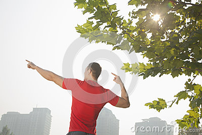Rear view of young muscular man stretching by a tree, arms raised and fingers pointing towards the sky in Beijing, China with lens