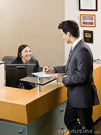 Receptionist Greeting Man At Front Desk Stock s