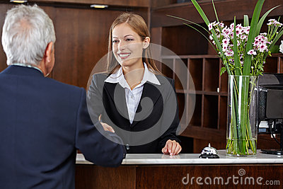 Receptionist greeting senior guest with handshake