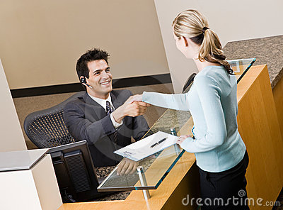 Receptionist greeting woman at front desk