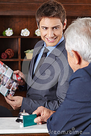 Receptionist in hotel giving brochure to guest