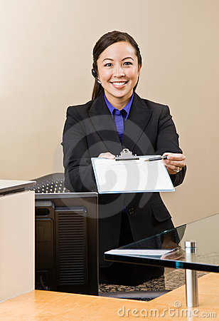 Receptionist offering clipboard and pen