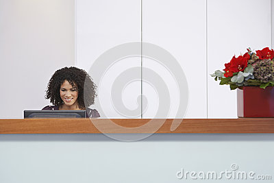 Receptionist Using Computer At Reception Desk