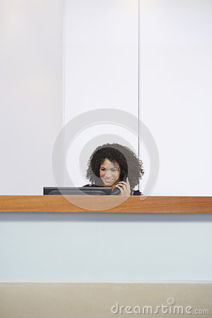 Receptionist Using Phone And Computer At Reception Desk