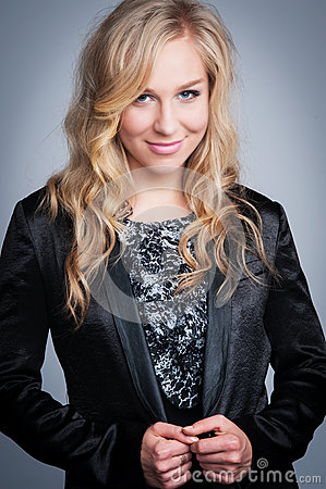 Recht blonde Frau in der schwarzen Jacke