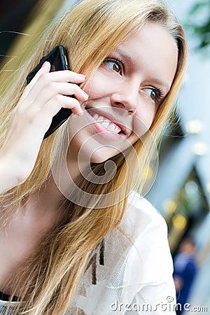Recht junge Frau, die auf dem Smartphone spricht