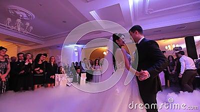 Recienes casados jovenes hermosos que bailan su primera danza cubierta por el humo blanco Celebración de la boda en el restaurant