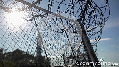 Recinto del filo spinato nell'ambito del fuoco del sole dentro fuori Estate prigione Fondo del faro stock footage