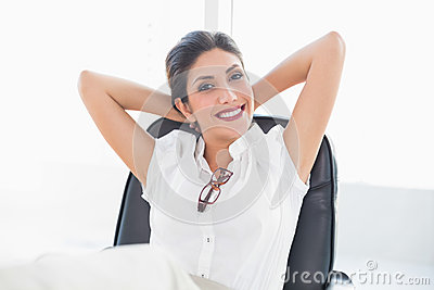 Reclining businesswoman sitting at her desk smiling at camera