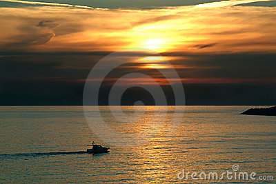Recreation boat sailing at sunset