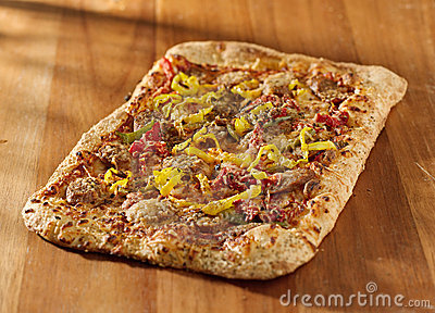 Rectangular gourmet pizza with sausage and colorfu