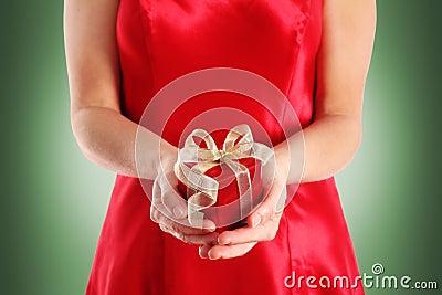 Rectángulo de regalo rojo en las manos de la mujer